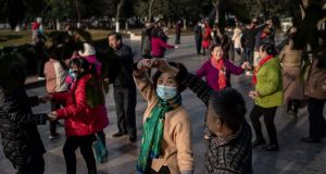 People dance in a public area along the Yangtze River in Wuhan on Monday  as the city marks the first anniversary of when China confirmed its first death from the Covid-19 coronavirus. Photograph: Nicolas Asfouri/AFP via Getty Images