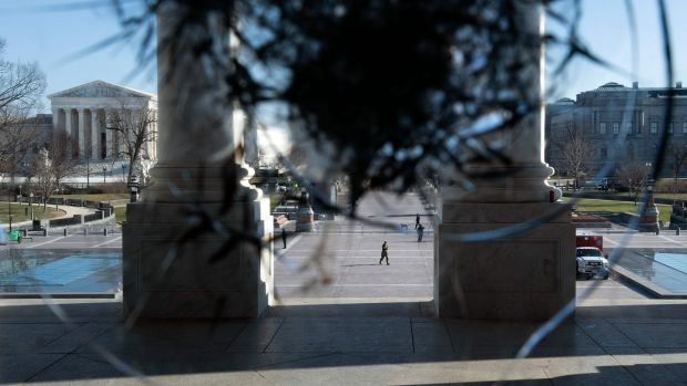 The US Supreme Court is seen through a broken window a day after a pro-Trump mob broke into the US Capitol. Photograph: Brendan Smialowski/AFP
