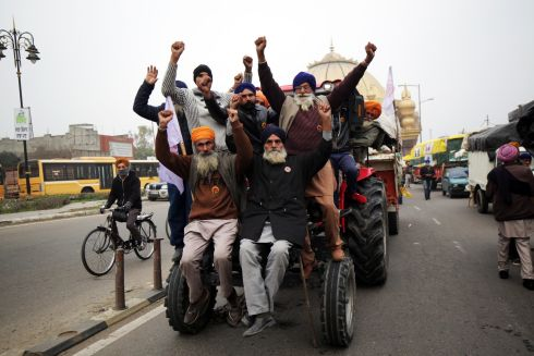 TAKING IT TO THE CAPITAL: Farmers pose for photographs in Amritsar, India, aboard a tractor before heading towards New Delhi to join other farmers taking part in a sit-in protest against new agricultural laws. The Supreme Court has put a stay on the controversial laws and has formed a four-member panel to hold talks with farmers on the issue. Photograph: Raminder Pal Singh/EPA