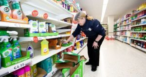 A supermarket worker wipes shelves with disinfectant wipes. File photograph: Tom Honan
