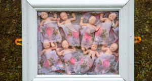 Framed baby dolls  pictured at a shrine in Tuam, Co Galway,  erected in memory of children buried at the site of the former home for unmarried mothers run by nuns. Photograph: Paul Fait/Getty Images
