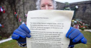 Carmel Larkin, a survivor of the Bon Secours mother and baby home, poses with a letter of apology from the Bon Secour Order, at a shrine in Tuam, Co Galway, which was erected in memory of up to 800 children who were allegedly buried at the site of the former home for unmarried mothers run by nuns. Photograph: Paul Faith/AFP via Getty Images