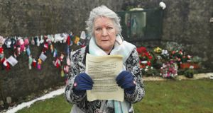 Carmel Larkin, who was born in the Tuam mother and baby home in 1949, holds a statement of apology from the Sisters of Bon Secours  at the grotto on Wednesday, on an unmarked mass grave at the site. Photograph: Niall Carson/PA Wire