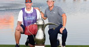 Bryson Dechambeau and  his caddie pose with the trophy after the American's  victory in the   2019 Omega Dubai Desert Classic in the UAE. Photograph:  Ross Kinnaird/Getty Images