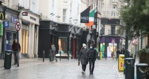 People walk along an almost deserted Grafton Street in Dublin city centre on Monday. Photograph: Niall Carson/PA Wire
