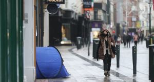A woman walks past the tent of a homeless person on Grafton Street in Dublin during lockdown. Photograph: Niall Carson/PA Wire