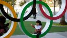 A young child poses with an Olympic Rings monument next to the National Stadium in Tokyo. Photo: Franck Robichon/EPA