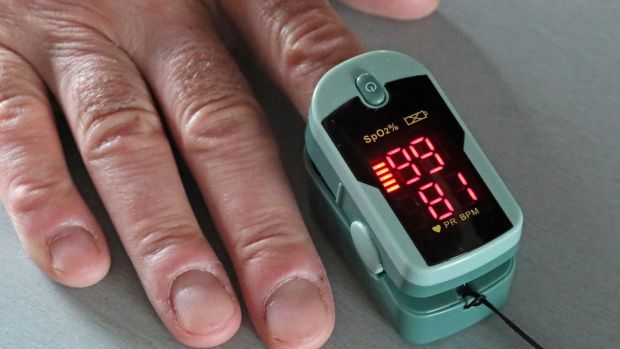 A pulse oximeter is placed on a person's finger to measure the oxygen level in the blood. Photograph: Vladimir Gerdo\TASS via Getty