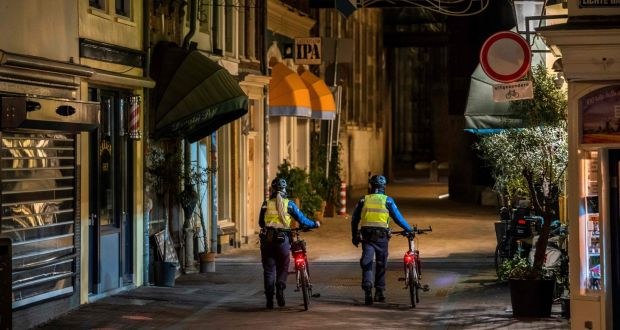 Law enforcement officers walk through the centre of Utrecht, the Netherlands, on Thursday. Latest figures showed 5,857 new cases of Covid-19 over the 24 hours to Thursday morning, a rise of 260. Photograph: Jeroen Jumelet/ANP/AFP via Getty Images