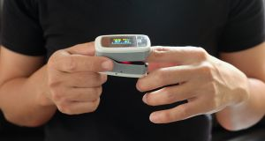 A pulse oximeter is placed on a person's finger to measure the oxygen level in the blood. Photograph: iStock