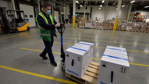 A member of the Cold Chain warehouse operations team moves 'shipper' boxes, which contain 'pizza boxes' boxes of the Pfizer/BioNTech vaccine vials. Photograph: Alan Betson