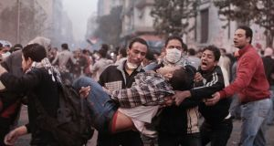 Protesters carry a wounded person away from Tahrir Square in Cairo on November 22nd, 2011. Photograph: Moises Saman/New York Times
