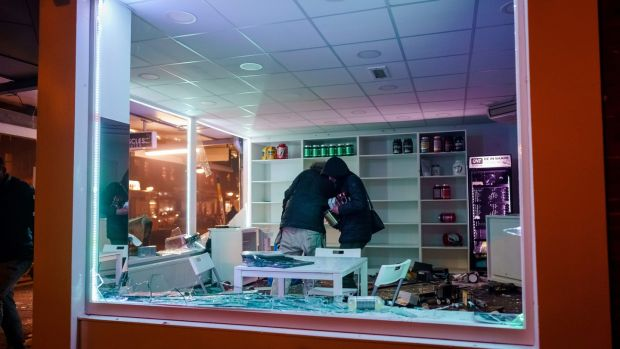 People loot a shop during clashes between police and a large group of young people in Rotterdam on Monday. Photograph: Marco de Swart/ANP/AFP via Getty Images