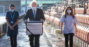 British prime minister Boris Johnson carries doses of the Oxford/AstraZeneca coronavirus vaccine for mobile distribution at Barnet FC's ground in north London, which is being used as a coronavirus vaccination centre. Photograph: Stefan Rousseau/Getty Images