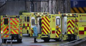 A medic in PPE stands amid ambulances outside the emergency department at the Mater hospital in Dublin. Photograph: Niall Carson/PA Wire