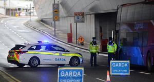 A Garda steps off a bus at a checkpoint in Dublin Airport during Covid-19 lockdown in late January, 2021. Photograph: Dara Mac Dónaill / The Irish Times