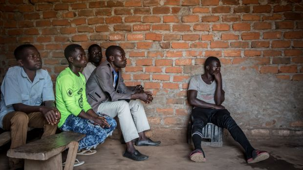 Men watch an English-language screening of the Dominic Ongwen ICC verdict, in his home village of Coorom, northern Uganda. Photograph: Sally Hayden