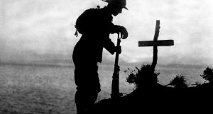 A soldier paying his respects at the grave of a colleague near Cape Helles, Ottoman Empire, where the Gallipoli landings took place in World War One, Dardenelles Front.  PA Wire