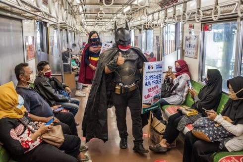 TO THE RESCUE: A couple dressed in superhero costumes walk through a commuter train to promote the prevention of Covid-19 transmission in Yogyakarta, Indonesia. Photograph: Agung Supriyanto/AFP/Getty