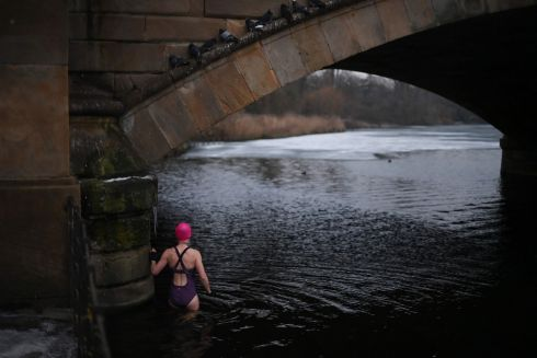 TAKING A DIP: A woman braves the freezing temperature to go for a swim in the Serpentine Lake in Hyde Park, London. Photograph: Daniel Leal-Olivas/AFP via Getty