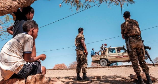 Ethiopian army soldiers watch as a pick-up truck with militia men passes by at Mai Aini refugee camp, in Ethiopia. Photograph Eduardo Soteras/AFP via Getty Images