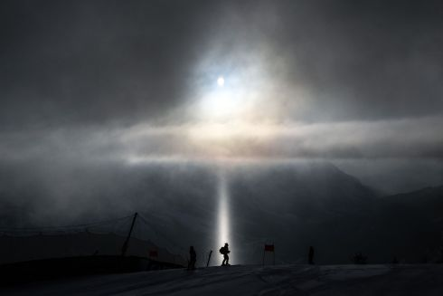 SPOTLIGHT: A coach stands in a ray of light, during the inspection of the ski trail prior to the start of the Women's Downhill, on February 13th, 2021 during the FIS Alpine World Ski Championships in Cortina d'Ampezzo, Italian Alps. Photograph: Fabrice Coffrini/AFP via Getty Images