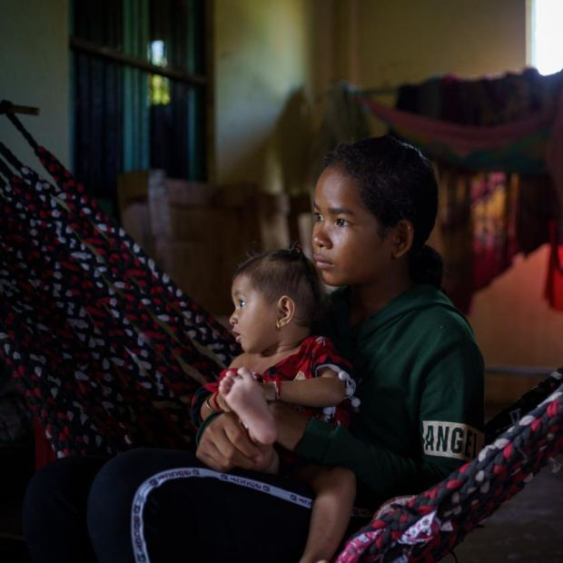 Phoun Phalla, and her baby nephew, in their house in Trapeang Thmor village. Phalla's parents gave consent for her to participate in the metagenomic study. Photograph: Thomas Cristofoletti/New York Times