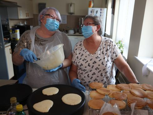 PANCAKE SALE: Tenants at Elmgrove Manor Sheltered Housing Scheme in Belfast, Linda Mulholland (left) and Sandra McGuicken, cooking pancakes to sell to tenants to raise money for a new lockdown garden. Photograph: Liam McBurney/PA Wire