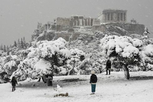 ATHENS SNOW: People walk near the snow covered Pnyx hill during heavy snowfall over Athens, Greece. Photograph: Louisa Gouliamaki/AFP via Getty