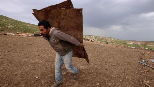 A man gathers material to build a temporary shelter after Israeli forces razed the Bedouin village of Khirbet Humsah. Photograph: Emmanuel Dunand