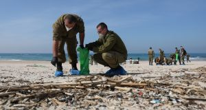 Israeli soldiers  cleaning a beach near the city of Rishon Lezion, Israel. Photograph: EPA/Abir Sultan