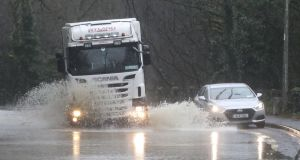 Vehicles drive through flood water in Mallow, Co Cork. Photograph: Niall Carson/PA Wire