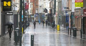 Members of the public brave the bad weather during the Covid-19 Coronavirus pandemic in Dublin's city centre on Tuesday. Photo:Gareth Chaney/Collins