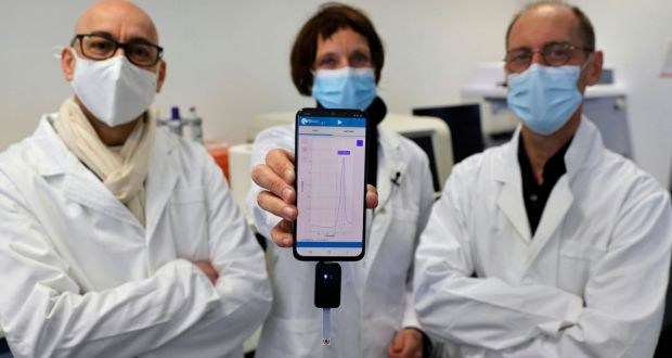 University of Lille researchers Rabah Boukherroub, Sabine Szunerits and David Devos with a smartphone showing CorDial-1 test result. Photograph: Pascal Rossignol/Reuters