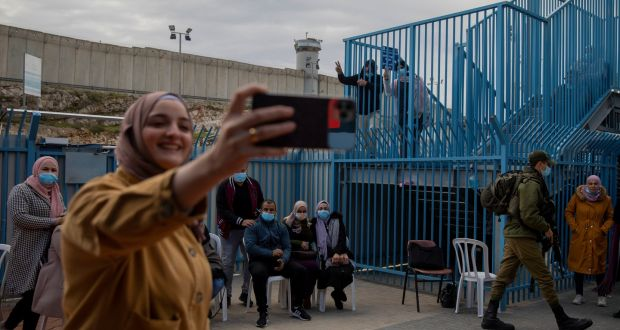Palestinians pose for a photograph after receiving the  coronavirus vaccine from an Israeli medical team at the Qalandia checkpoint between the West Bank city of Ramallah and Jerusalem. Photograph: Oded Balilty/AP Photo