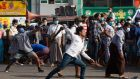 Pro-military supporters hurl stones at residents near the central railway station in Yangon on Thursday. Photograph: EPA