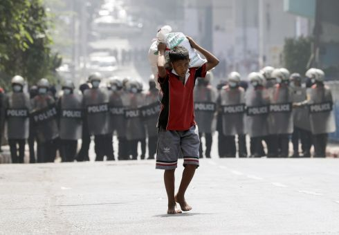 MYANMAR UNREST: A boy carries a sack of rice past anti-riot police officers blocking a road during a protest against the military coup in Yangon, Myanmar. Photograph: Lynn Bo Bo/EPA