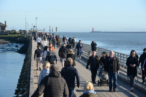 Crowds walk the wooden bridge at Bull Island, Dublin. Photograph: Dara Mac Dónaill/The Irish Times