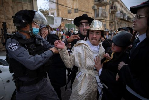 Ultra-Orthodox Jews, some wearing costumes, scuffle with police officers during celebrations of the Jewish holiday of Purim, in the Mea Shearim ultra-Orthodox neighbourhood of Jerusalem. The Jewish holiday of Purim commemorates the Jews' salvation from genocide in ancient Persia, as recounted in the biblical Book of Esther. Photograph: Oded Balilty/AP Photo
