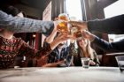 A group of friends toasting in a pub, holding their glasses high above the table. Lockdown restrictions have left Irish bar owners with little to cheer about, although they are still generating some income, as noted by latest data from the CSO.