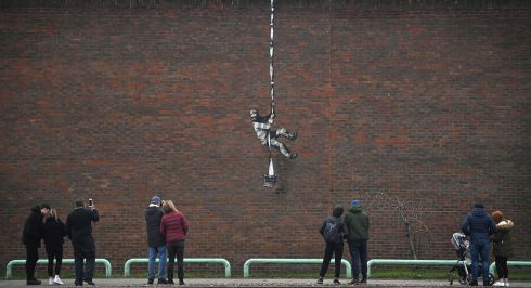 BALLED OF READING GAOL? People pause to look at an artwork bearing the hallmarks of street artist Banksy which has appeared on the side of Reading Prison in Reading, west of London. The picture shows a prisoner, possibly resembling famous inmate Oscar Wilde, escaping on a rope made of bedsheets tied to a typewriter. The work has not yet been claimed by Banksy. Photograph: Ben Stansall/AFP/Getty
