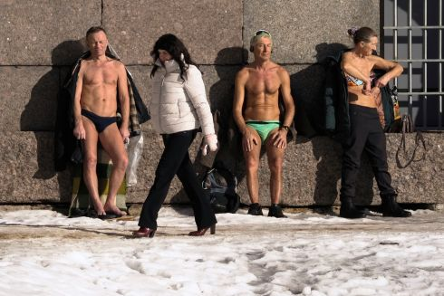 WARMING UP: Swimmers look to warm themselves in the sun against a wall of Peter and Paul fortress on the bank of the Neva River in St Petersburg, Russia, as snow lies on the ground. The air in St Petersburg warmed up to 4 degrees Celsius on Tuesday. Photograph: Dmitri Lovetsky/AP Photo