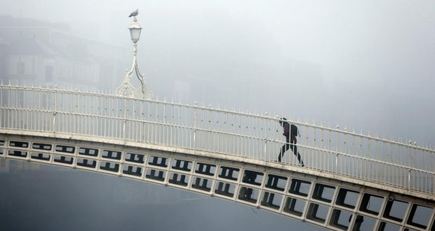 A lone pedestrian on the Ha'penny Bridge, Dublin, in early morning fog. Photograph: Nick Bradshaw