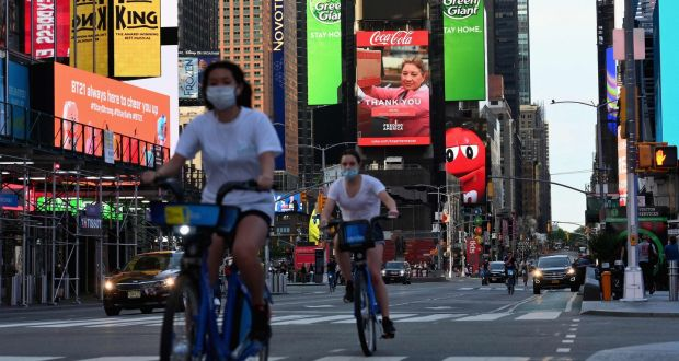 People wearing face masks ride their bikes through Times Square in May 2020. Photograph:  Angela Weiss/AFP via Getty Images