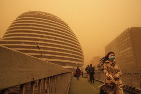 SANDY CITY: Commuters wear protective masks during a sandstorm in Beijing, China. The northern part of the country was hit with the storm on Monday, causing air quality indexes for PM 2.5 and PM 10 to rocket and the cancellation of flights. Photograph: Kevin Frayer/Getty