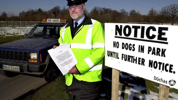 Park ranger Brendan Kinsella handing out a notice to people in the Phoenix Park asking them not to enter the park in order to minimise the risk of spreading foot-and-mouth disease to the deer in the park in March 2001.