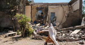 A woman walks in front of a damaged house which was shelled as federal-aligned forces entered the city, in Wukro, north of Mekele, on March 1st. Photograph: Eduardo Soteras/AFP