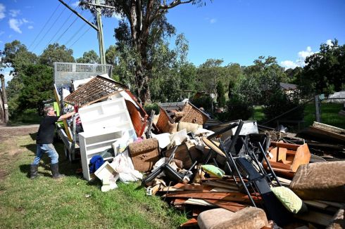 CLEAN UP: A man piles up damaged possessions outside of his house in a suburb of Sydney, Australia, amid a massive clean-up effort after days of floods. Photograph: Saeed Khan/AFP via Getty