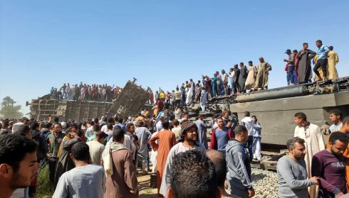Crowds gather at the scene of an overturned train carriage in Sohag province, Egypt. At least 32 people were killed and 84 injured when two trains collided in central Egypt on Friday, said health ministry officials . Photograph: Stringer/EPA
