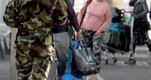 A member of the Defence Forces directs passengers arriving at Dublin Airport  to a mandatory 12-day hotel quarantine. Photograph: Brian Lawless/PA Wire